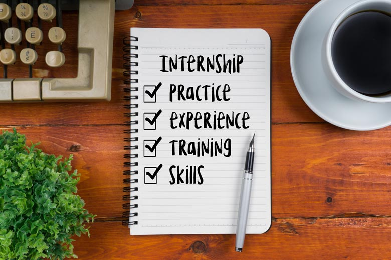 """Notebook with pen on wooden desk background; notebook has title, """"Internship,"""" with checklist underneath with following items: practice, experience, training skills"""
