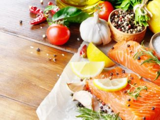 Salmon being prepared with veggies, herbs, spices