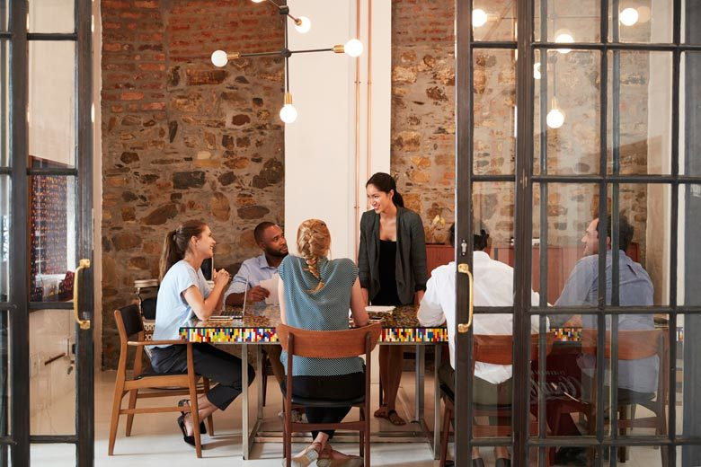 A group of people working together on a project around a table with an exposed brick wall in the background