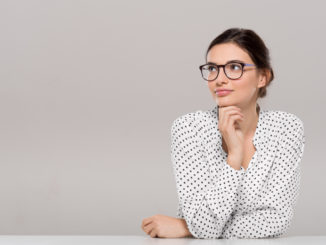 Young woman wearing glasses and thinking with hand on chin.