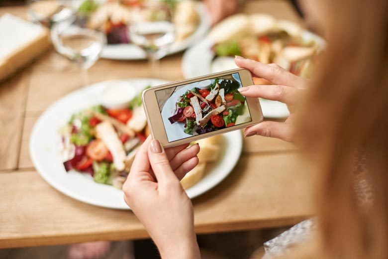 A close up of a woman's hands taking a picture of her meal, a salad