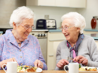 Senior women enjoying meal together in kitchen at home
