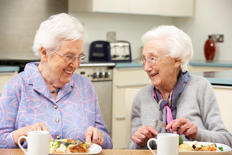 Senior women enjoying meal together in kitchen at home
