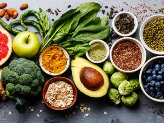 A variety of fresh foods — greens, Brussels sprouts, avocado, apple, broccoli and grains — grouped together on a gray background