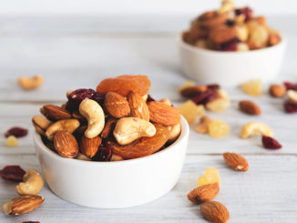 mixed nuts and dried fruit in wooden bowl on wooden table top view. Walnut, pistachio, almond, hazelnut, cashews, apricot, berry, banana, pineapple, Healthy food and snack