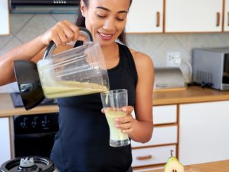 Woman in workout gear pouring herself a smoothie milkshake