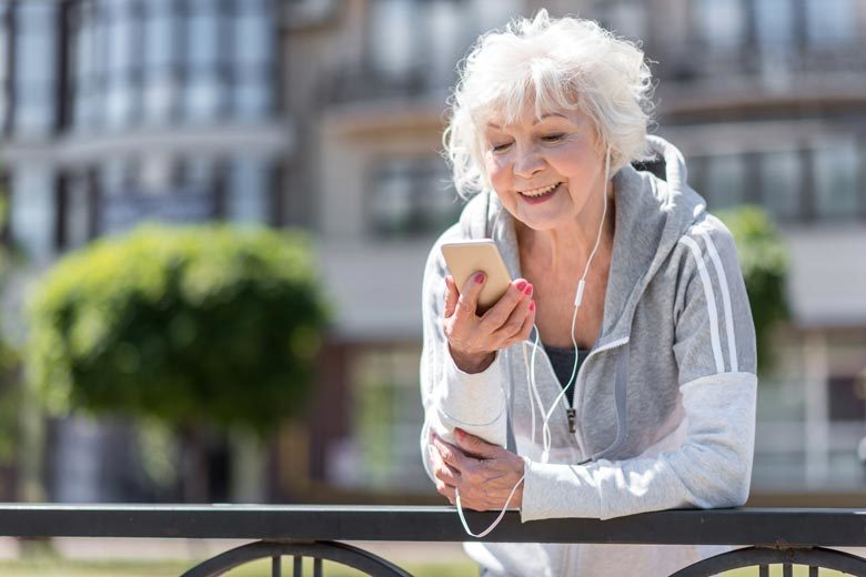 An older woman looking at her phone while on a walk around the city