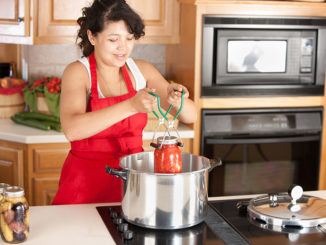 Woman canning tomatoes in her kitchen