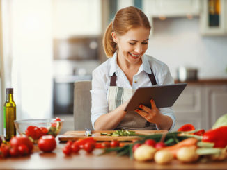 happy woman preparing vegetables in kitchen on prescription with tablet