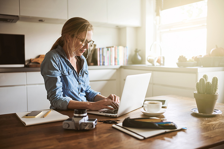 Young woman sitting in her kitchen working on a laptop