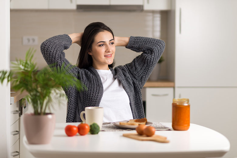 Young woman stretching during breakfast time at home