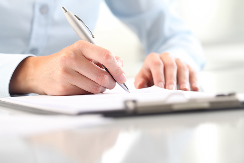 Woman's hands writing on sheet in clipboard with a pen