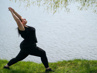 Woman doing yoga, relaxing near lake
