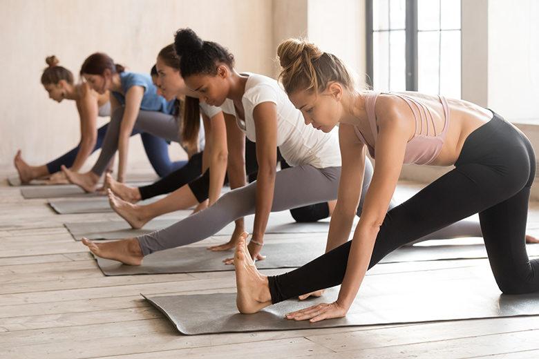 Group of women practicing yoga lesson, doing Ardha Hanumanasana exercise